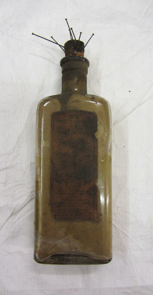 Figure 3. Victorian cod-liver oil bottle containing pins and urine, found in a chimney in Padstow, Cornwall. Currently held at the Horniman Museum. Photograph by C. Houlbrook, January 2016.