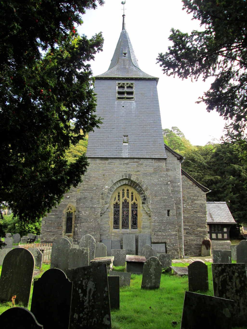 The distinctive steeple of St Twrog's church, viewed from amongst the ancient yews. The stone can be seen at bottom right. © Remy Dean