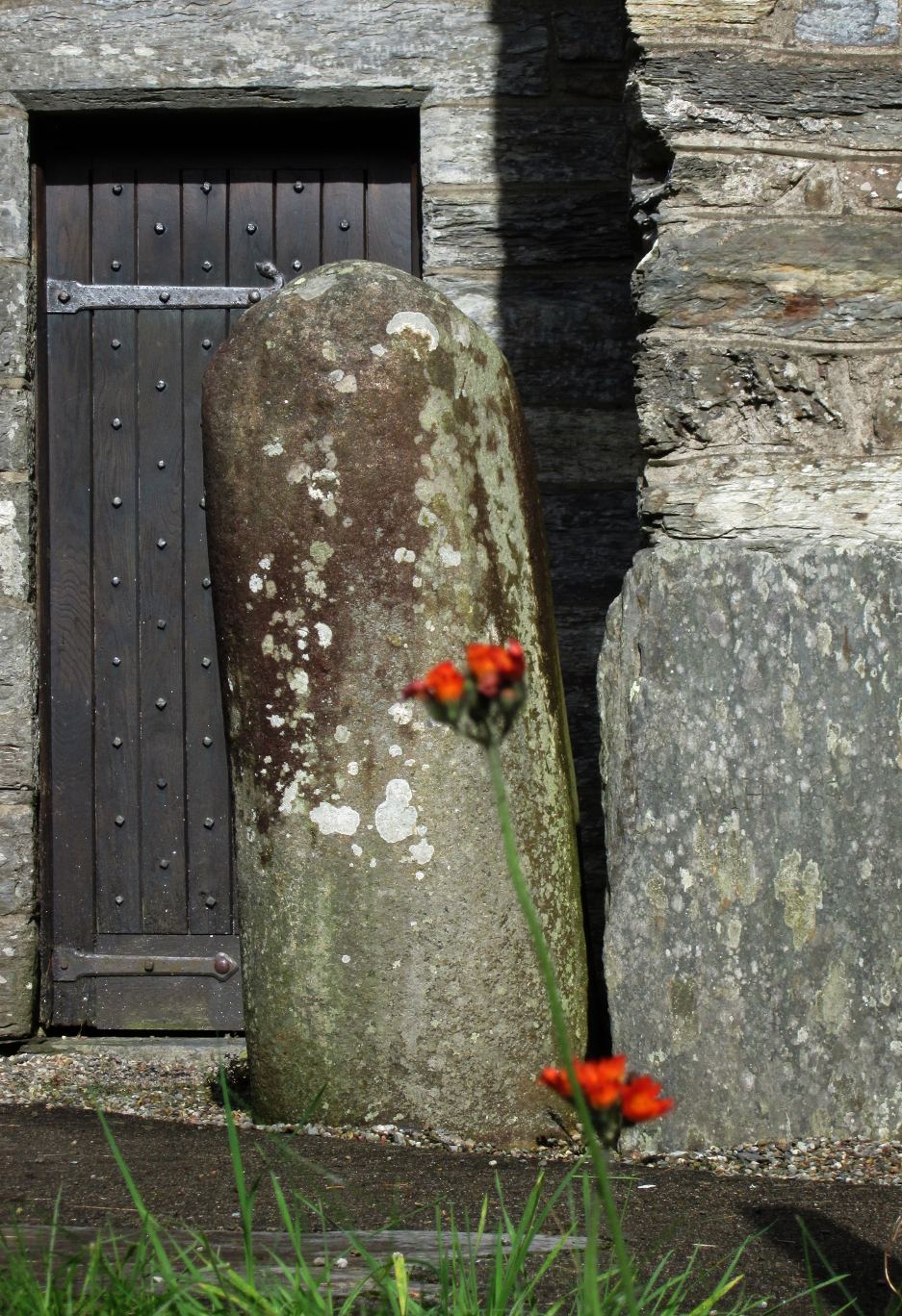 The stone, situated just outside the belfry door. It bears marks said to be left by the grip of St Twrog's hand. © Remy Dean
