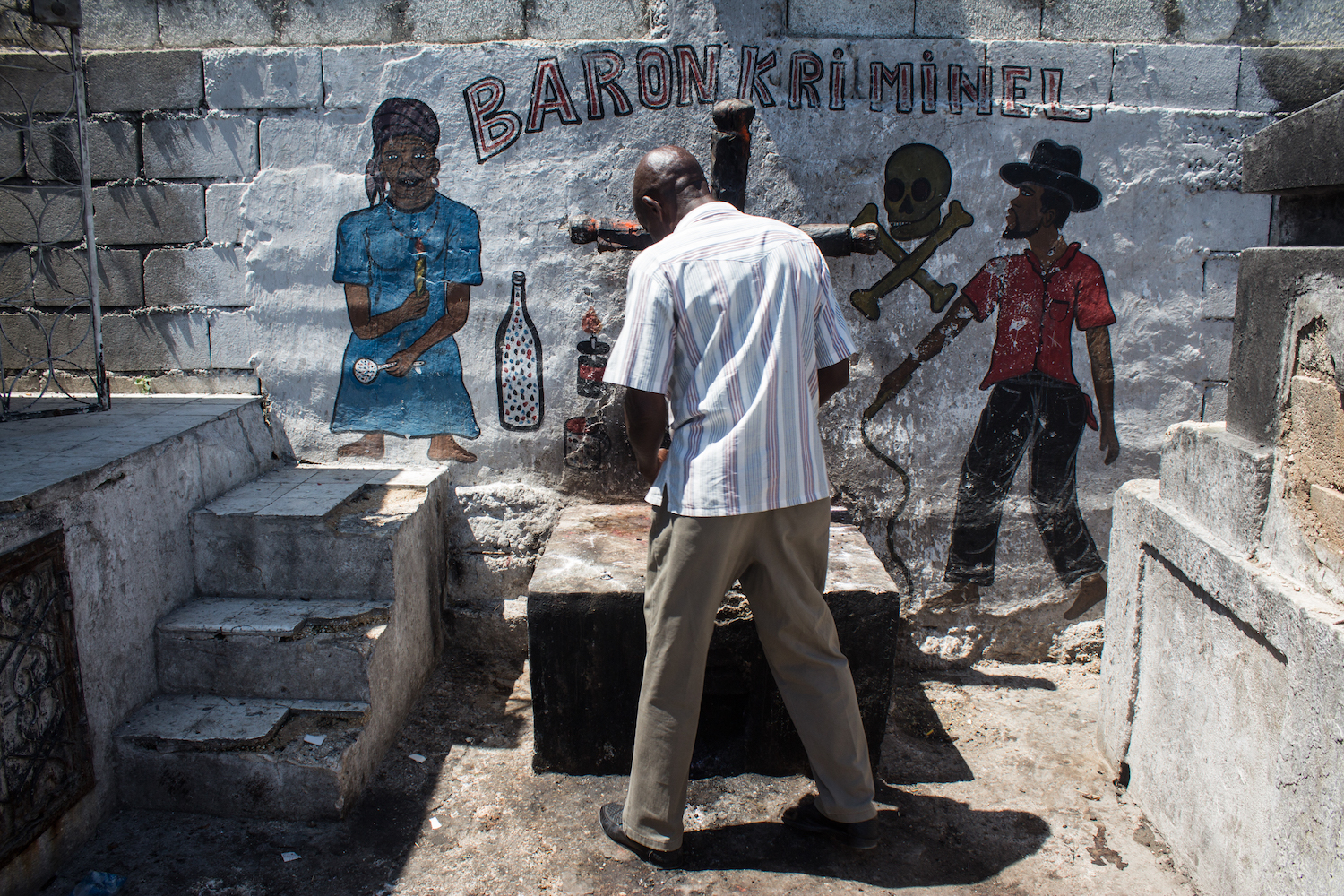 A Haitian man makes an offering to Baron Kriminel at a fire-stained altar. © Darmon Richter http://www.thebohemianblog.com/2015/04/haitian-vodou-port-au-prince.html