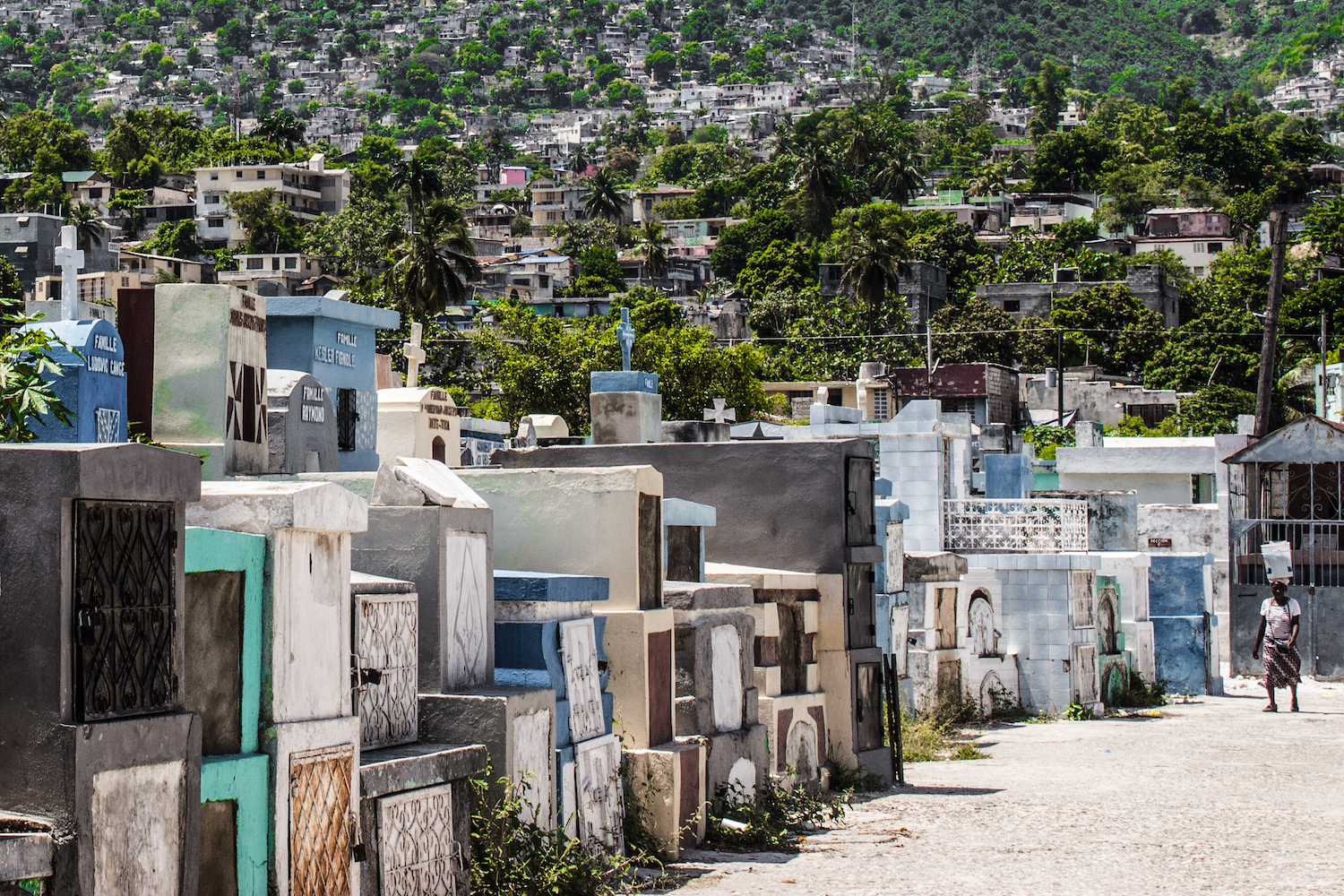 A woman walks between the rows of graves at Le Grand Cimetière. Port-au-Prince, Haiti. © Darmon Richter http://www.thebohemianblog.com/2015/04/haitian-vodou-port-au-prince.html