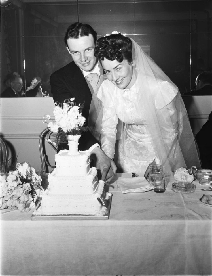 Photo of a couple with their wedding cake