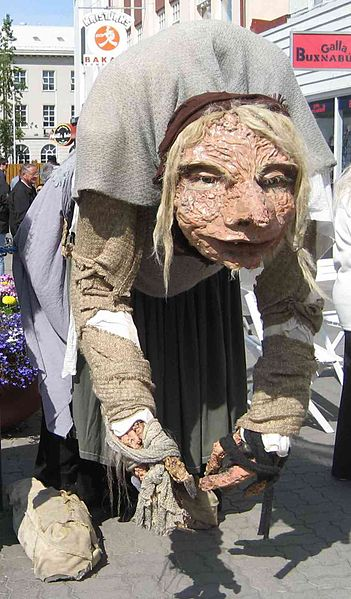 Large street puppet of a bent over old woman