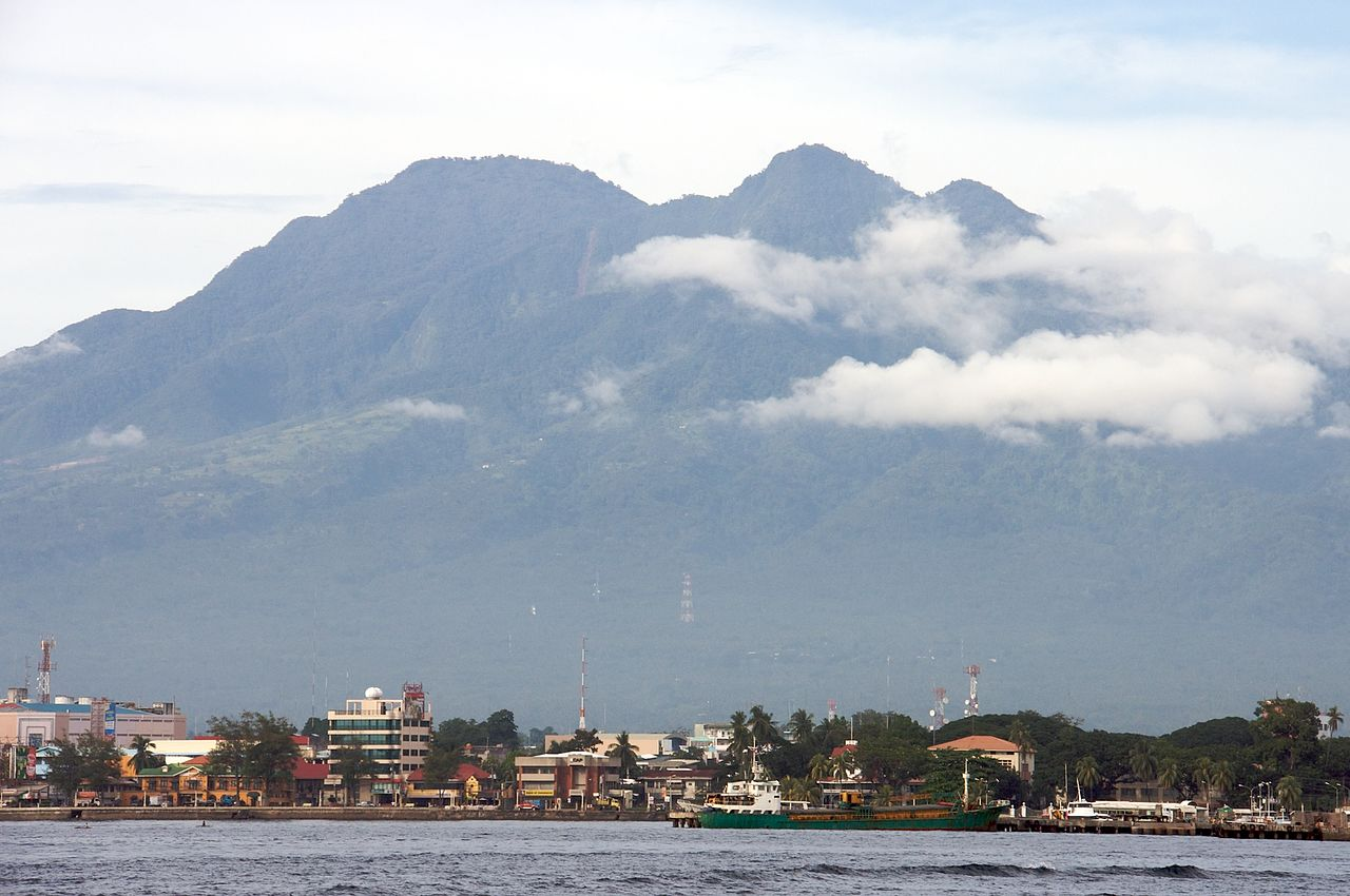 Shot of a city by the sea, with a towering mountain in the background