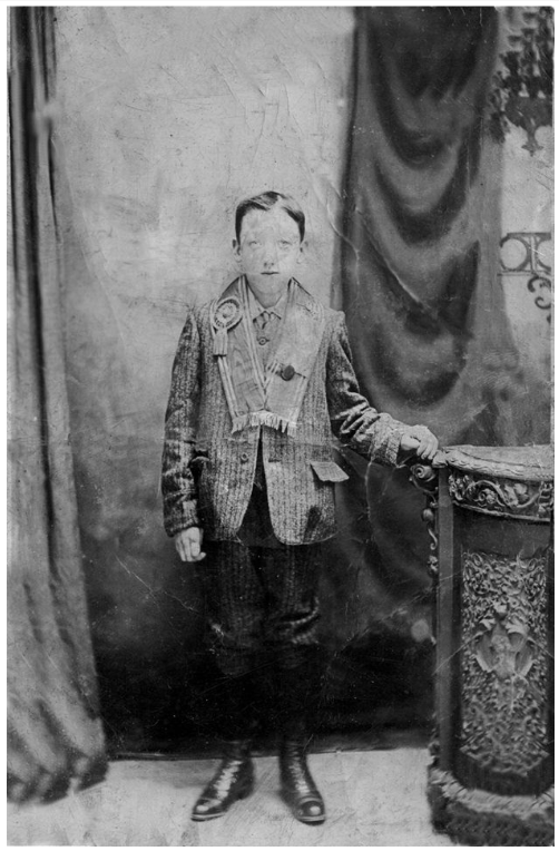 Black and white photo of a boy with an orange sash