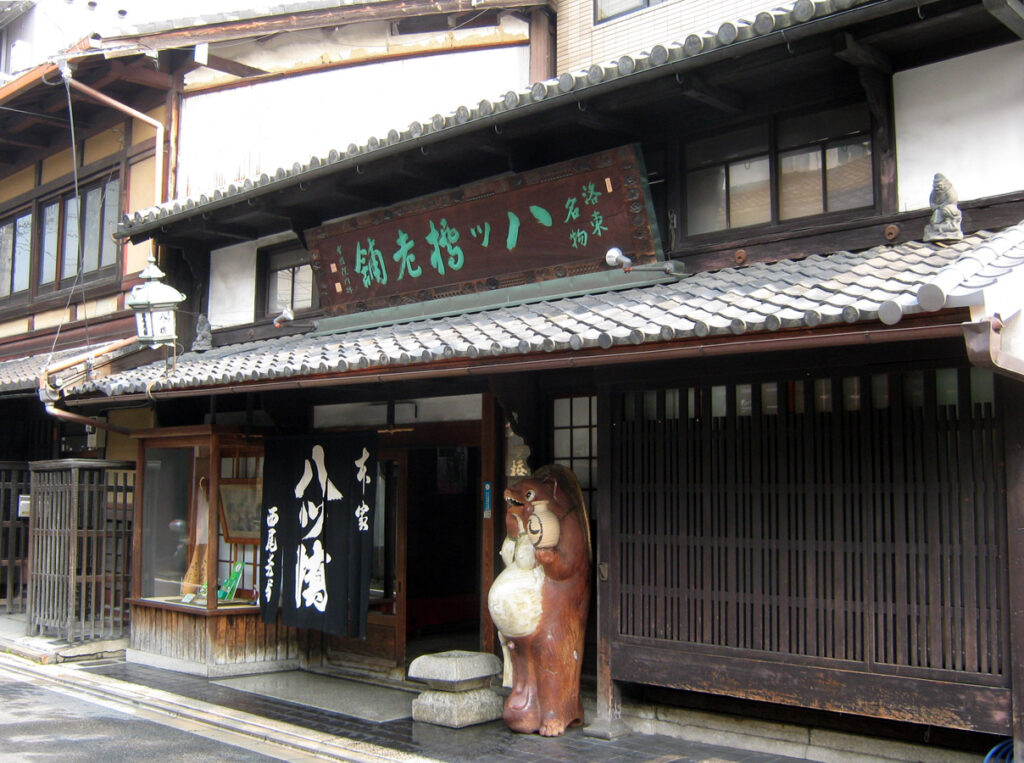 A tanuki statue outside the Honke Nishio Yatsuhashi sweet shop in Kyoto. By ja:利用者:Mariemon - ja:ファイル:Nishio5538.JPG, CC 表示 3.0, https://commons.wikimedia.org/w/index.php?curid=44994634