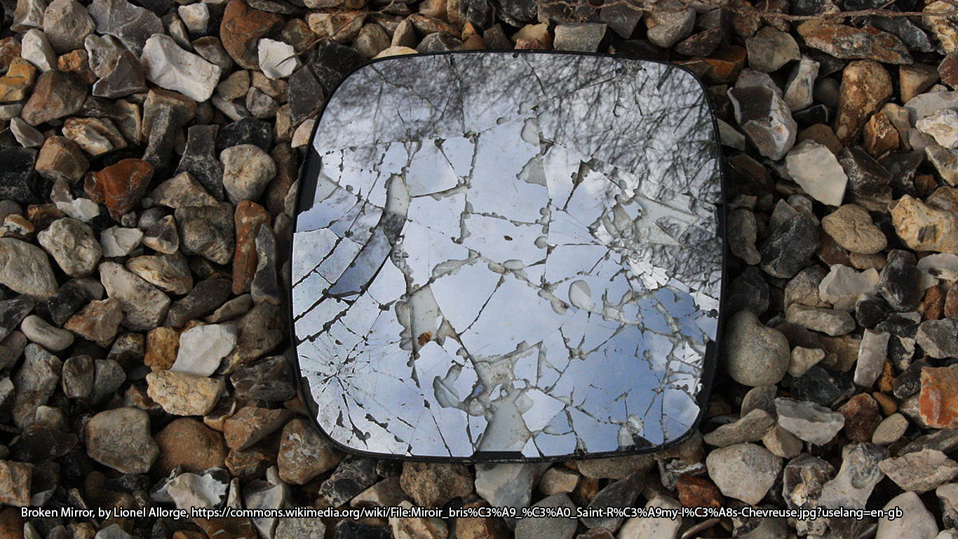 Photograph of broken mirror on top of gravel.