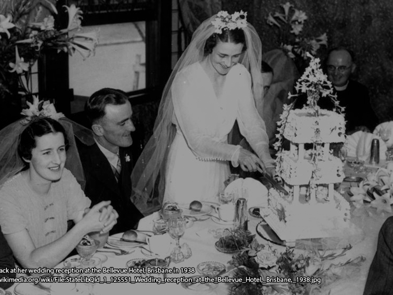 Woman cutting a wedding cake with people seated around a dinner table.