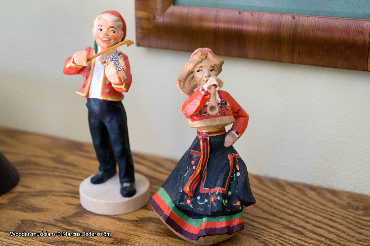 Two carved wooden figures: A man playing a fiddle, and a woman playing a wind instrument.