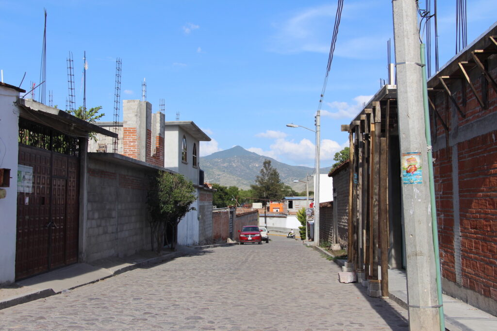 Streets of Mitla; the sacred mountain of Guirún lies in the distance. © Hilary Morgan Leathem