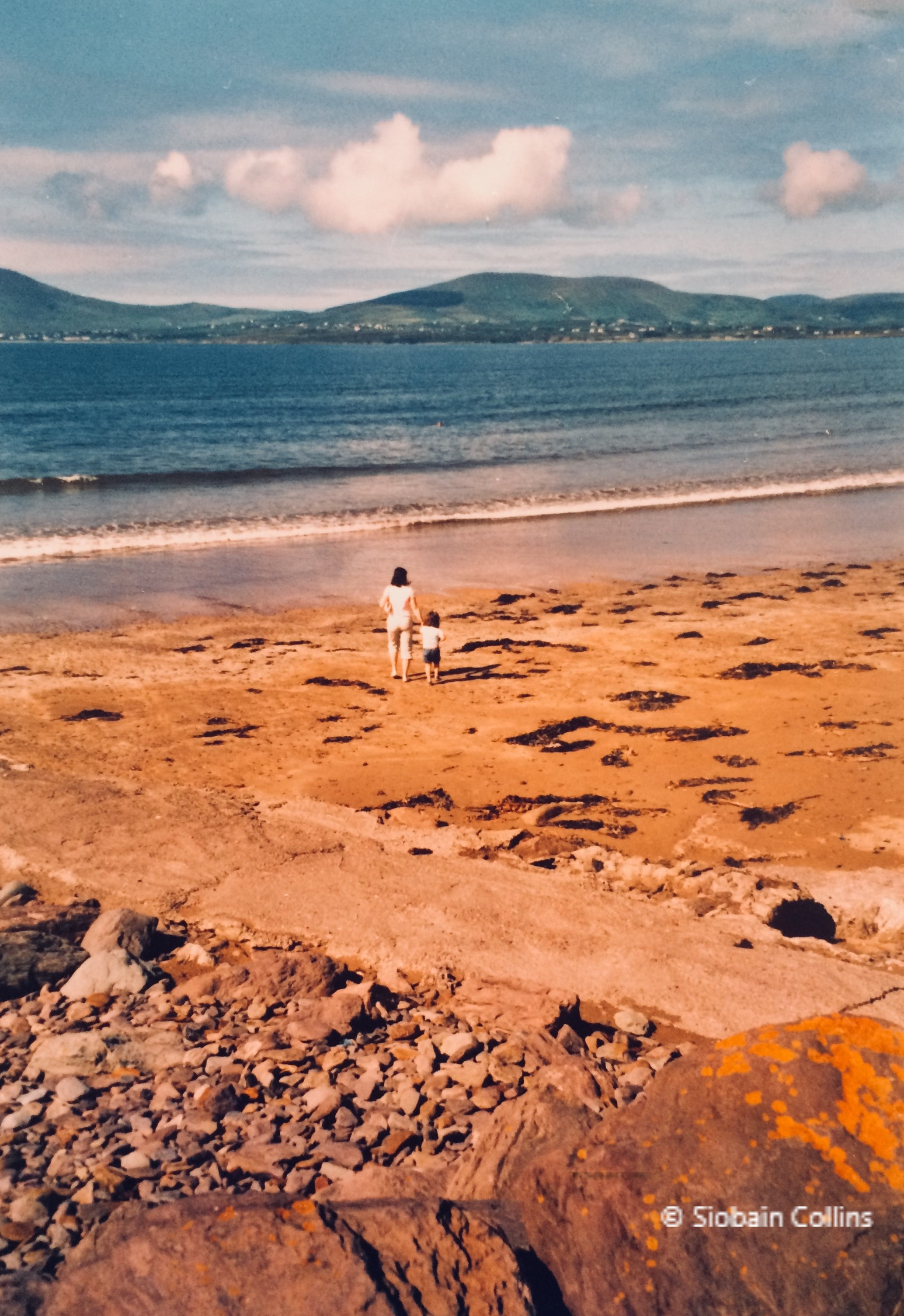 Irish beach with hills in the background, and shoreline in the foreground, a teenager and a child both female holding hands