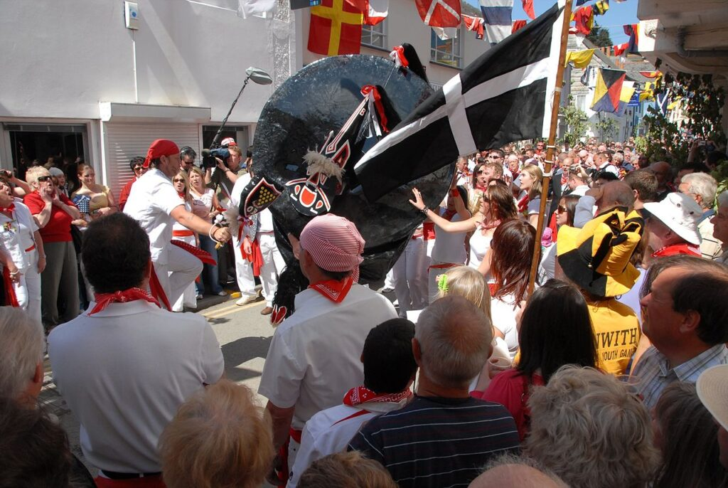 Padstow's old 'Obby 'Oss parades with the teaser and his club to the left. The tail of the 'Oss is at the top with the head pointed down. Teaser and 'Oss dance as they travel the streets amongst a crowd singing in praise of summer. Cornwall's national flag, St Piran's white cross on a black background, unfurls in the foreground.By Bryan Ledgard, CC BY 2.0, https://commons.wikimedia.org/w/index.php?curid=58269367