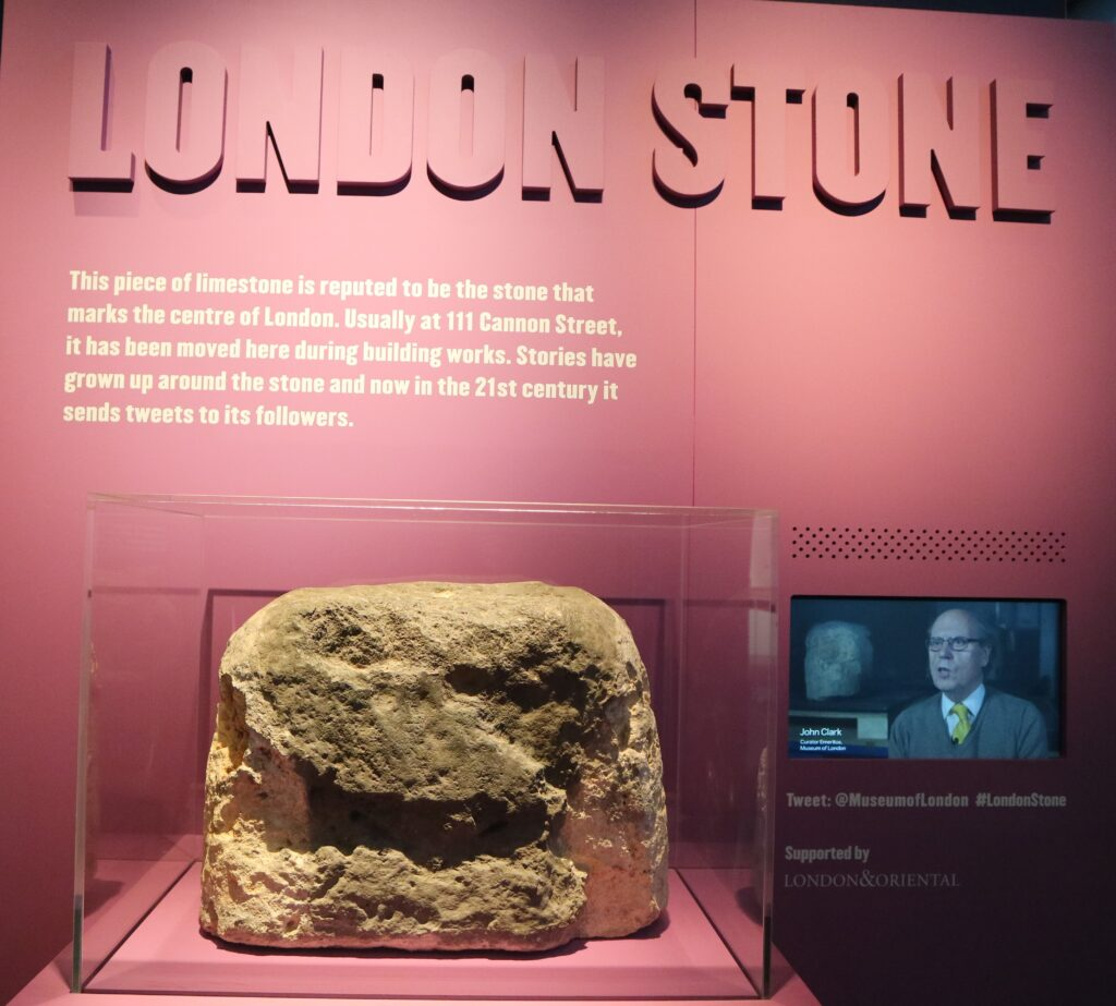 "The London Stone sitting in a glass case at the Museum of London. Text behind the stone says ""This piece of linestone is reputed to be the stone that marks the centre of London. Usually at 111 Cannon Street, it has been moved here during building works. Stories have grown up around the stone and now in the 21st century it sends tweets to its followers."