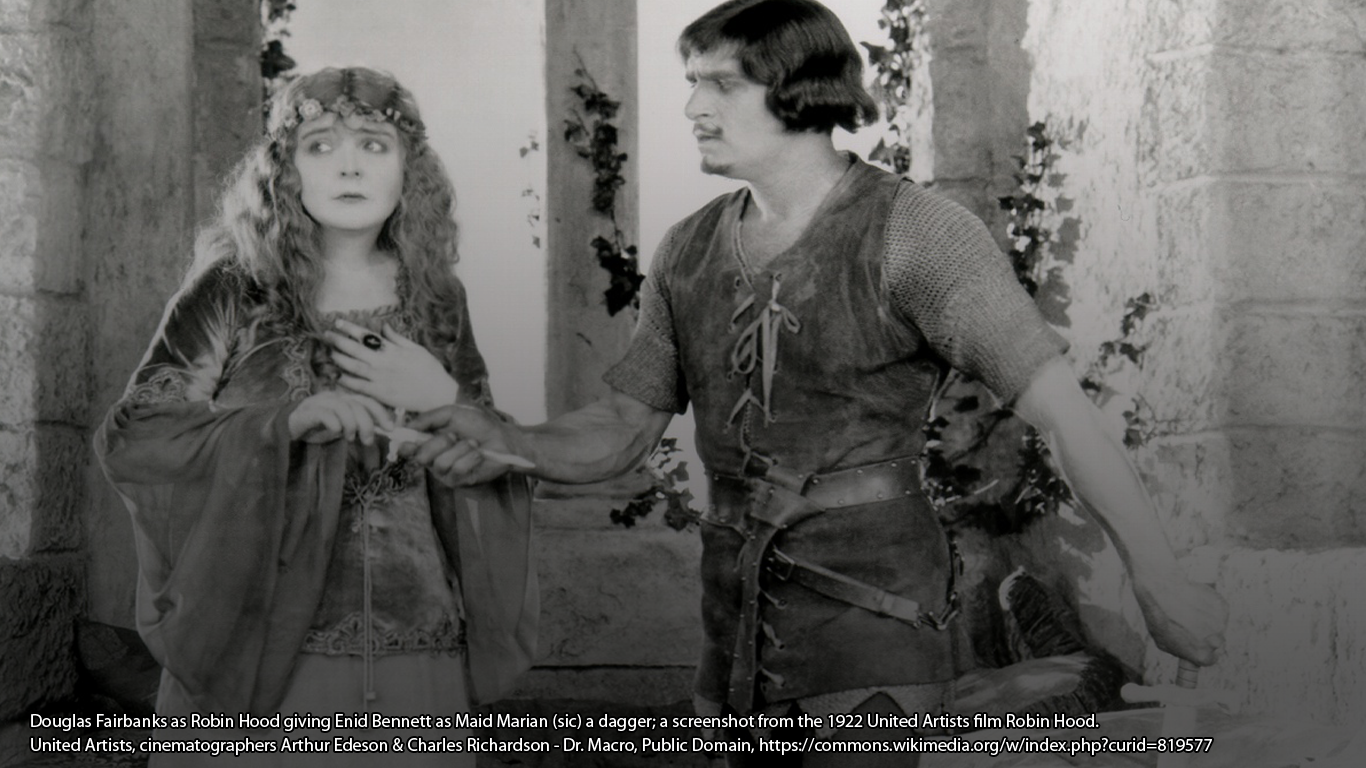 Douglas Fairbanks as Robin Hood giving Enid Bennett as Maid Marian (sic) a dagger; a screenshot from the 1922 United Artists film Robin Hood. United Artists, cinematographers Arthur Edeson & Charles Richardson - Dr. Macro, Public Domain, https://commons.wikimedia.org/w/index.php?curid=819577