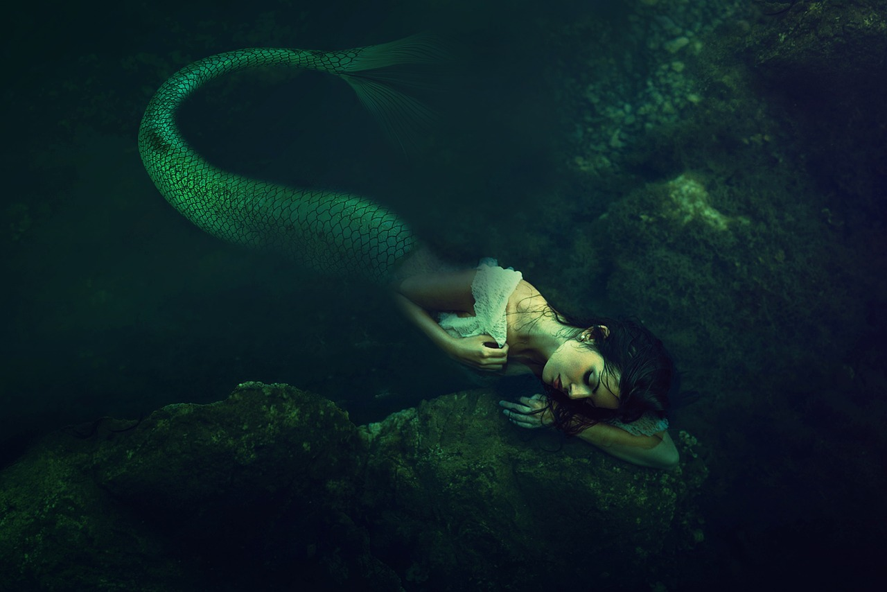 Mermaid underwater resting her head on a rock.