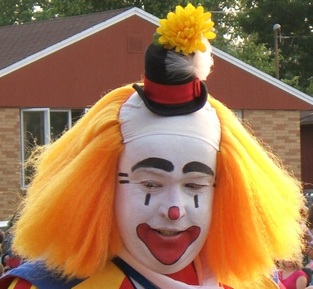 Clown with orange hair. By photo taken by flickr user *Micky* - flickr, CC BY 2.0, https://commons.wikimedia.org/w/index.php?curid=1887219