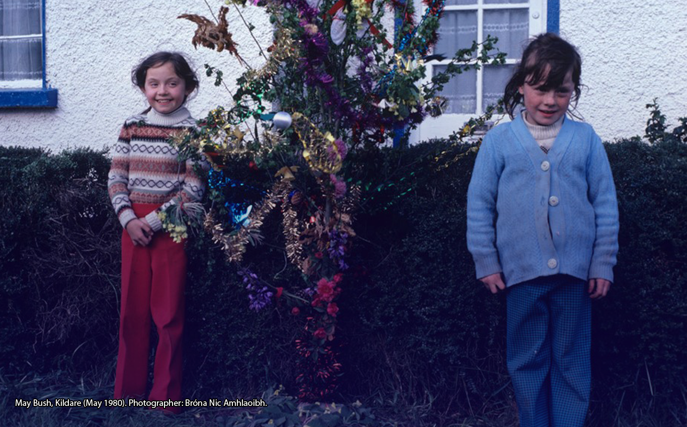 Two children standing in front of a decorated May Bush, Kildare (May 1980). Photographer: Bróna Nic Amhlaoibh.