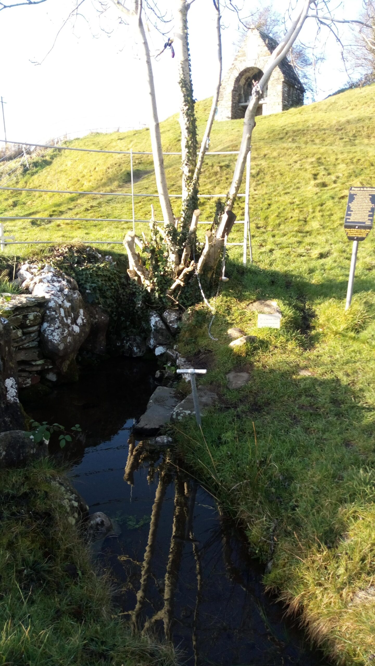 St Keeran's Well, Co. Meath. Rags hang from the tree and there is a ladle attached to a chain to retrieve the water. By Conchúr Mag Eacháin (photographer).