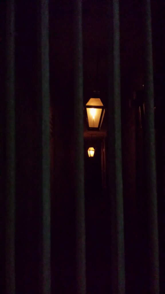 Flickering lamps in a dark New Orleans passage © Randi Samuelson-Brown