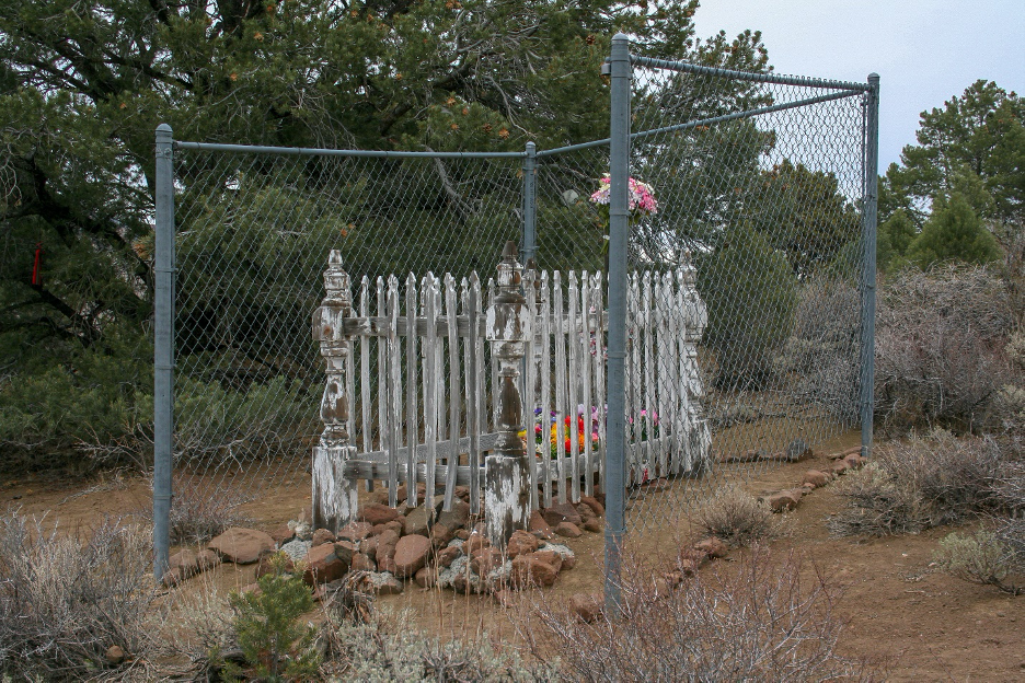 Figure 3. The invented location of Julia Bulette's final resting place includes wood likely taken from another grave. The chain-link fence protects the focus of veneration from wild horses who would trample it. Photograph by Ronald M James.
