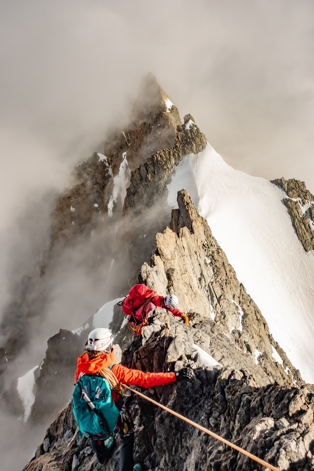 Two climbers at a peak of the Alps